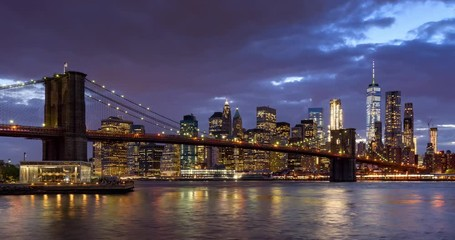 Fotomurales - Time-lapse of Lower Manhattan Financial District skyscrapers, Brooklyn Bridge, and East River with passing clouds at twilight. Manhattan, New York City