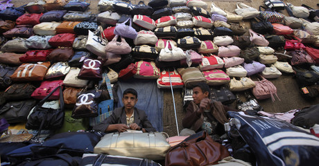 Street vendors wait for customers at their stall in a market in the Old City of Sanaa