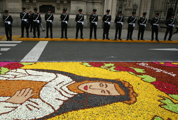 Police guard next to a flower carpet with the image of Santa Rosa de Lima (Saint Rose) at the main plaza during celebrations of Saint Rose of Lima, patroness of Latin America and the Philippines, in Lima