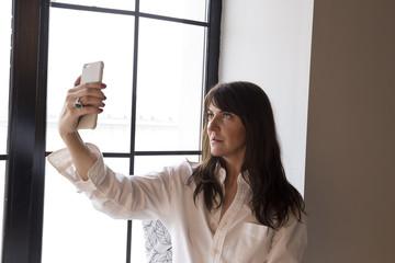 Beautiful business woman taking a selfie by the window