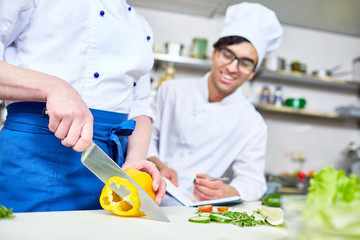 Trainee in uniform cutting pepper with chef near by