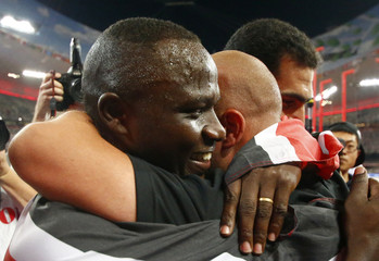Winner Yego of Kenya hugs a coach next to second placed El Sayed of Egypt after competing at the men's javelin throw final during the 15th IAAF World Championships at the National Stadium in Beijing