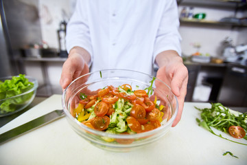 Chef showing cooked salad in bowl