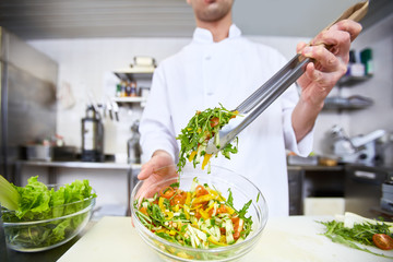 Chef taking salad from bowl to serve
