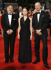 "Director Kiyoshi Kurosawa, cast members Eri Fukatsu and Tadanobu Asano pose on the red carpet as the arrive for the screening of the film ""Kishibe no tabi"" at the 68th Cannes Film Festival in Cannes"