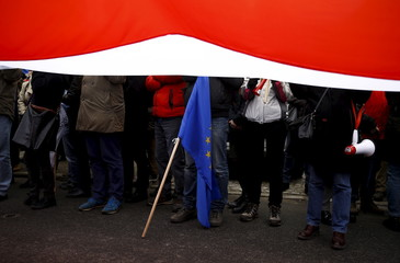 An EU flag is seen under a giant Polish flag held by people taking part in a march demanding their government to respect the country's constitution in front of the Constitutional Court in Warsaw