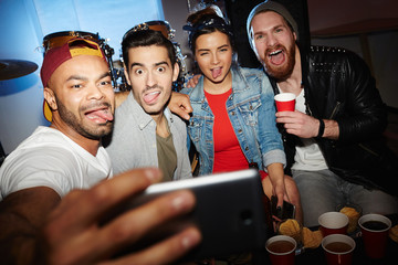 Group of modern young people chilling at night club party, posing for selfie photo, grimacing and having fun