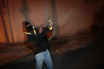 A villager aims a weapon at the entry of Castanas, in the outskirts of Guatemala City