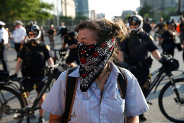 A demonstrator stands in front of rows of police officers during protests outside the Republican National Convention in Cleveland, Ohio