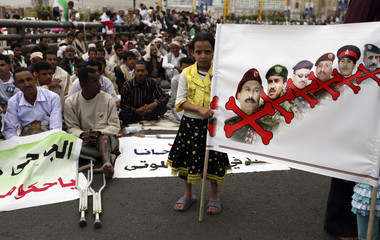 Girl carries a poster during a rally to demand the prosecution of the family of former Yemeni President Saleh in Sanaa