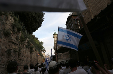 Israelis carry flags as they walk in Jerusalem's Old City during a parade marking Jerusalem Day