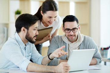 Group of employees looking at data in laptop