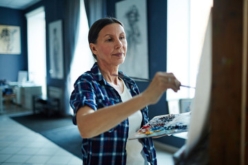 Portrait of elegant mature woman painting oil picture on canvas in art-studio, looking inspired and enjoying process