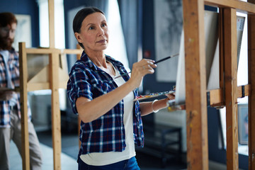 Portrait of inspired mature woman painting picture on easel standing in row of students in art class