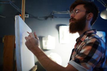 Portrait of inspired young red-haired man drawing outline on canvas ready to paint picture in dim studio
