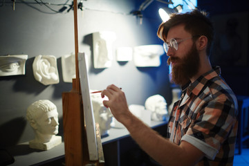 Portrait of inspired young red-haired man painting picture of plaster heads in art studio, looking focused and concentrated