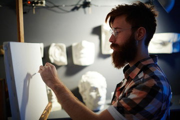 Portrait of inspired young red-haired man drawing first lines of picture on blank white canvas