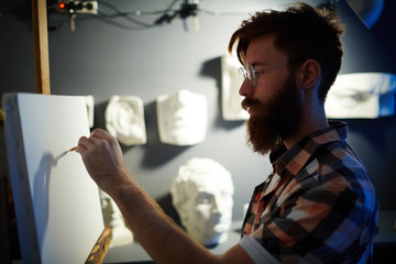 Portrait of modern bearded artist drawing first lines of picture on blank white canvas in dim lighting