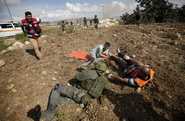 Wounded Palestinian and an Israeli border policeman fall along with a medic during clashes over tension in Jerusalem's al-Aqsa mosque, near the occupied West Bank city of Ramallah