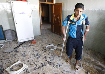 An injured man stands inside a house, where a girl was killed when a rocket hit it, in the Iraqi border town of al-Qaim in Anbar province