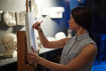 Portrait of young talented woman drawing plaster head models on blank white canvas in art studio