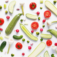 Fresh vegetables in a cut on a white background. Pattern from vegetables. Food background.  Cucumbers, tomatoes and zucchini in a cut.