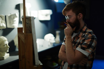 Side view portrait of contemporary bearded artist looking at his panting on canvas deep in thought while working in art studio