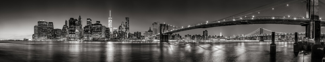 Acrylic Prints New York City Panoramic Black and white view of Lower Manhattan Financial District skyscrapers at twilight with the Brooklyn Bridge and East River. New York City