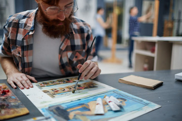 Portrait of contemporary bearded artist working in art studio painting pictures looking focused and concentrated