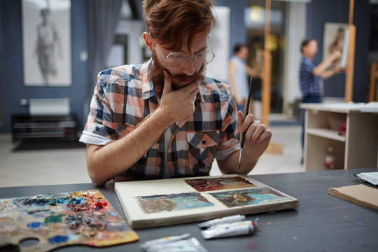 Portrait of contemporary bearded artist working in art studio painting pictures thinking and looking focused