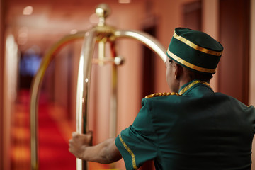 Back view portrait of African-American bellhop pushing luggage cart delivering bags to hotel rooms in hallway, helping guests
