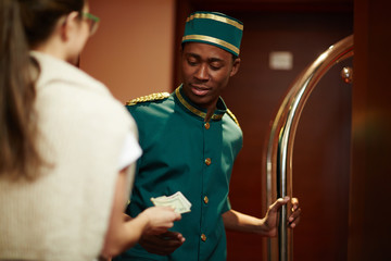 Portrait of smiling young African boy working as bellhop in luxury hotel, getting tip from woman guest for delivering luggage to room