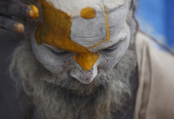 Hindu holy man, or sadhu, applies paint to his forehead at his ashram on the premises of Pashupatinath Temple in Kathmandu