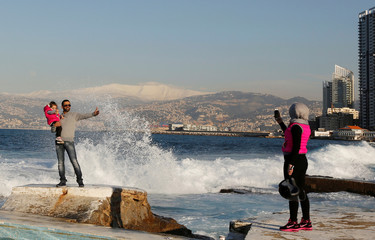 A woman takes photos of her husband and child on a cold day from the private beach of the American University of Beirut at the Mediterranean coast, with snow-covered Mount Sannine seen in the background in Beirut