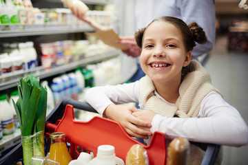 Portrait of cute little girl smiling happily leaning on shopping cart while buying groceries in supermarket with family