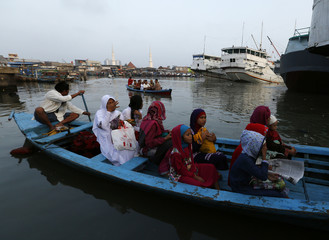 A Muslim family rides a wooden boat as they head for Eid al-Fitr prayers in Jakarta