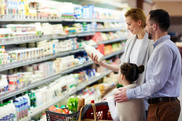 Portrait of happy family shopping in grocery store: buying milk in dairy product department