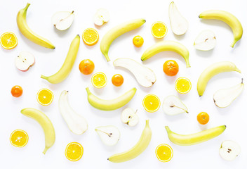 Fresh fruit in a cut on a white background.  Food background. Pattern of bananas, tangerines and pears.