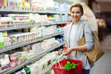 Portrait of beautiful blond woman with shopping basket buying groceries in supermarket and smiling looking at camera