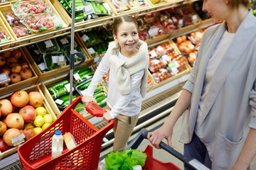Portrait of little girl pushing little shopping cart helping mom buy groceries in supermarket