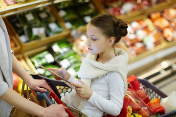 Portrait of little girl sitting in shopping cart and entertaining herself with digital tablet while her parents grocery shopping in supermarket