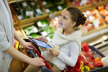 Portrait of smiling little girl sitting in shopping cart and entertaining herself with digital tablet while her parents grocery shopping in supermarket