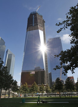 A worker mows the lawn beneath One World Trade Center in New York