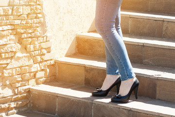 Woman in light blue jeans and black high-heeled shoes, walking on the stairs. Fashion wallpaper, with sunlight flash effect