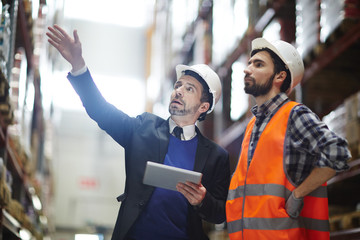 Businessman with touchpad pointing at upper shelf with goods while talking to worker