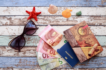 Travel concept: seashells, sunglasses, passport, money and journal on vintage table