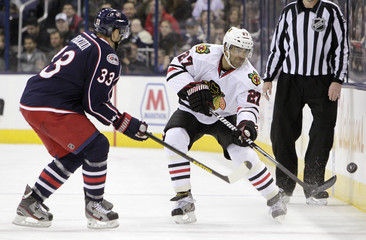 Blackhawks' Oduya clears the puck as Blue Jackets' Aucoin defends during their NHL hockey game in Columbus