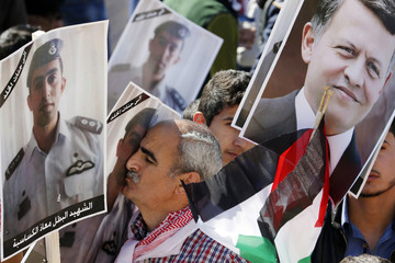 A Jordanian protester kisses a poster bearing the image of Jordanian pilot Muath al-Kasaesbeh during a rally to show their loyalty to King Abdullah and against the Islamic State in Amman