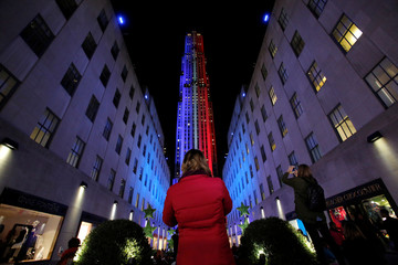 People take pictures 30 Rockefeller Plaza as it is lit in the colors of the Democratic and Republican parties ahead of the U.S presidential election in Manhattan, New York, U.S.