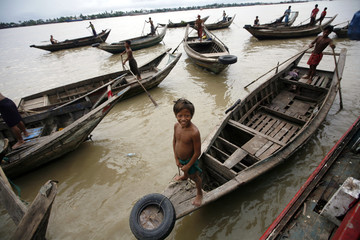 Men row their boats along the banks of the Yangon River in the outskirts of Yangon